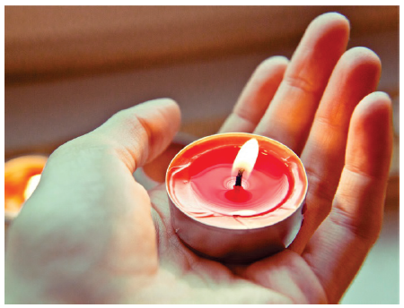 Image is a close-up of a hand holding a tea-light candle.