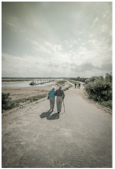 Image shows an eldery couple walking along a shoreline.