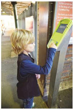 Image is of a young boy using a myki card reader. Photograph courtesy of Public Transport Victoria