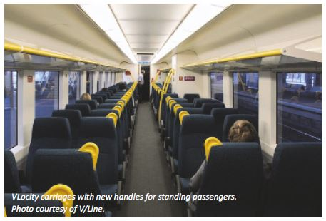 Photo showing the inside of a VLocity train carriage with handles fitted for standing passengers