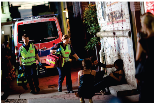 Two paramedics attending a call out in an alleyway at night. They are attending to a girl who is slumped on the floor. Photo courtesy of Ambulance Victoria.
