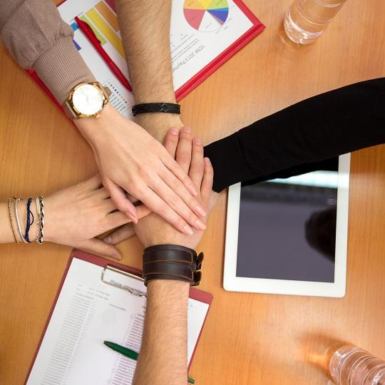 Image shows hands together team unity concept. Photo courtesy of Lucky Business/Shutterstock.com
