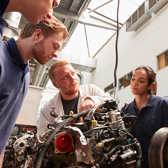 Apprentices leaning around an engine to listen to a teacher. Photo courtesy of Monkey Business Images/Shutterstock.com