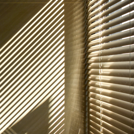 Shadows cast onto a wall by venetian blinds.